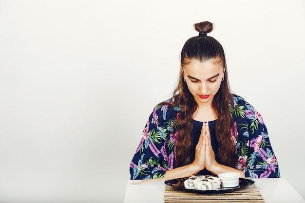 Schönes mädchen, das sushi in einem studio isst