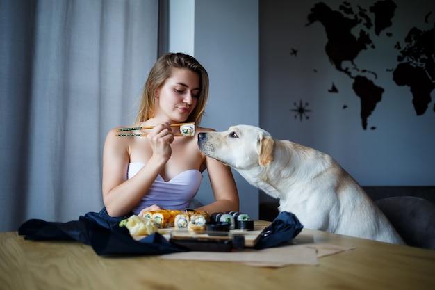 Schönes mädchen, das sushi-nahaufnahme mit ihrem hund labrador isst, lächelt und hält eine sushi-rolle mit stäbchen. gesundes japanisches essen.