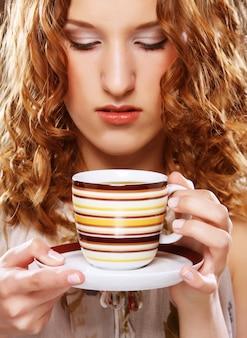 Schönes mädchen, das tee oder kaffee trinkt.