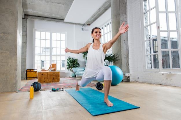 Schönes mädchen, das training und yoga zu hause am morgen macht