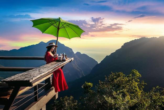 Schönes mädchen, das tropfkaffee am sonnenaufgang aussichtspunkt in pha hi dorf, chiang rai provinz, thailand macht