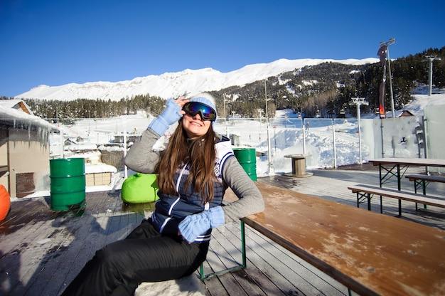 Schönes mädchen, das vom skifahren in einem café-skigebiet am fuße der berge ruht