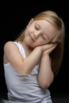 Schönes mädchen, das vorgibt zu schlafen, während es mit den händen unter der wange und den geschlossenen augen posiert.
