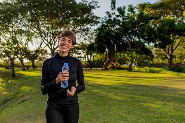 Schönes mädchen, das wasser von einer flasche im park trinkt.