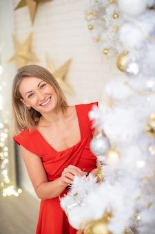 Schönes mädchen, das weihnachtsbaum verziert. eine junge lächelnde frau bereitet einen weihnachtsbaum für den urlaub vor. blondine im roten kleid. üppiger weißer weihnachtsbaum mit goldenen kugeln
