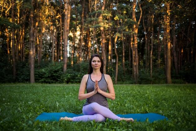 Schönes mädchen, das yoga im park bei sonnenuntergang tut