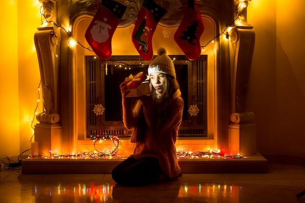 Schönes mädchen, das zu weihnachten im dunklen wohnzimmer sitzt und in die geschenkbox schaut