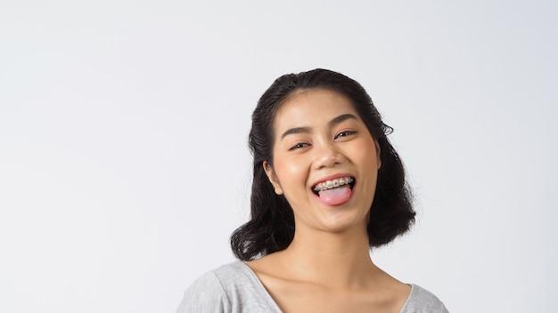 Schönes mädchen der zahnspange, das auf einer kamera lächelt, weiße zähne mit blauen klammern zahnpflege