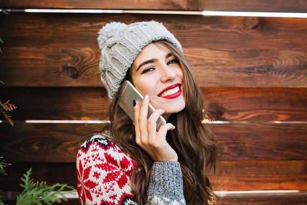 Schönes mädchen des nahaufnahmeporträts mit langen haaren und roten lippen auf holz. sie trägt eine warme wintermütze und einen pullover, telefoniert und lächelt.