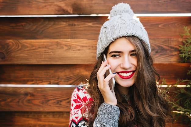 Schönes mädchen des nahaufnahmeporträts mit langen haaren und schneeweißem lächeln mit gestrickter mütze auf holz. sie trägt einen warmen pullover, telefoniert und lächelt zur seite.