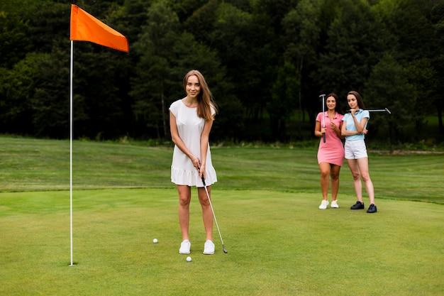 Schönes mädchen des vollen schusses, das golf spielt