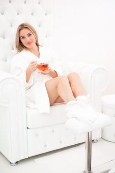 Schönes mädchen entspannt sich in einem weißen bademantel mit einer tasse tee in den händen im spasalone.