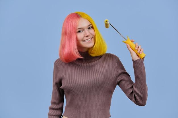 Schönes mädchen färbt ihr haar mit baurolle, teenager mit modischer gelber rosa frisur. färbung, salon, mode, frisuren, schönheitskonzept, blauer studiohintergrund der farbe