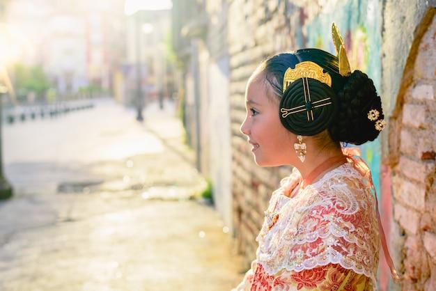Schönes mädchen fallera, das das traditionelle valencianische kostüm von fallas trägt