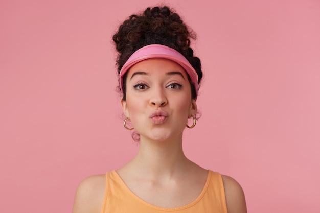 Schönes mädchen, flirty frau mit dunklem lockigem haar brötchen. tragen sie ein rosa visier, ohrringe und ein orangefarbenes trägershirt. hat sich geschminkt. schließt die lippen zu einem kuss