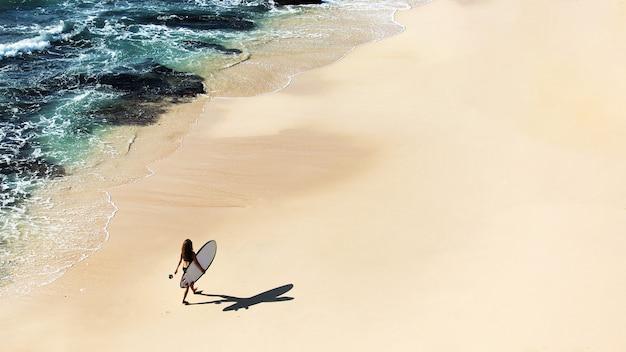 Schönes mädchen geht mit einem surfbrett an einem wilden strand. tolle aussicht von oben.