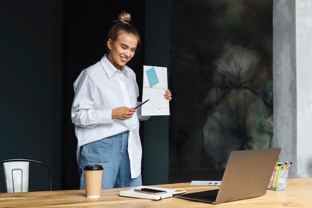 Schönes mädchen hält dokumente in der hand und kommuniziert über webkamera.