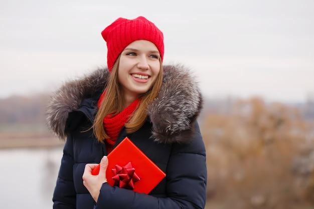Schönes mädchen hält eine schachtel mit einem geschenk in den händen das konzept für den valentinstag