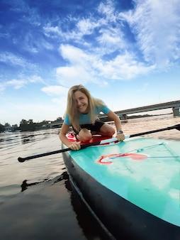 Schönes mädchen hat sich auf einem sup-paddleboard auf die knie gesetzt, lächelt und schaut in die kamera