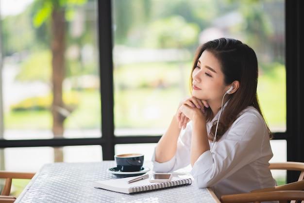 Schönes mädchen hören musik im café und trinken etwas kaffee
