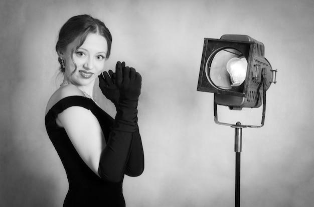 Schönes mädchen im abendkleid und langen handschuhen posiert im studio