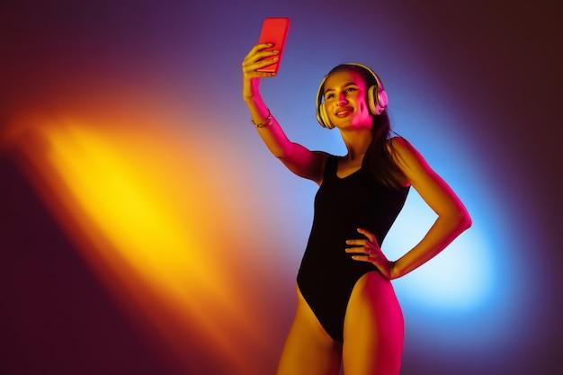 Schönes mädchen im badeanzug auf neonstudiohintergrund
