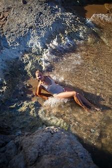 Schönes mädchen im badeanzug liegt an einem sandstrand im meerwasser