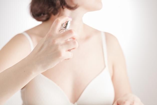 Schönes mädchen im badetuch verwendet parfüm