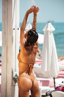 Schönes mädchen im beigen bikini, der dusche nimmt, während mit zurück auf strand steht.