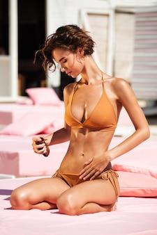 Schönes mädchen im bikini, das auf strandbett mit körperölflasche in der hand sitzt. porträt der jungen dame im beige badeanzug beim sonnenbaden am strand. hübsches mädchen, das sonnenöl auf ihrem körper für sonnenbräune am strand schmiert