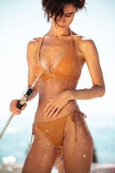 Schönes mädchen im bikini mit schlauchleitung am strand. porträt der dame im beige badeanzug, der strandsand von ihrem körper am strand abspült. junges nettes mädchen, das wasser vom schlauch am strand gießt