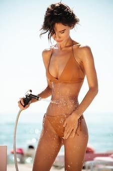 Schönes mädchen im bikini mit schlauchleitung am strand. porträt der hübschen dame im beige badeanzug, der strandsand von ihrem körper am strand abspült. junges mädchen, das wasser vom schlauch beim stehen am strand gießt