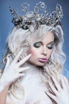 Schönes mädchen im bild der schneekönigin. saubere haut, weißes haar, eine krone auf dem kopf. im studio fotografiert.