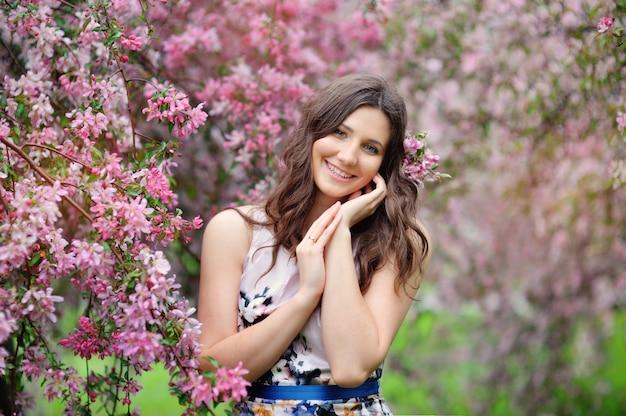 Schönes mädchen im frühlingsgarten unter den blühenden bäumen mit rosa blumen