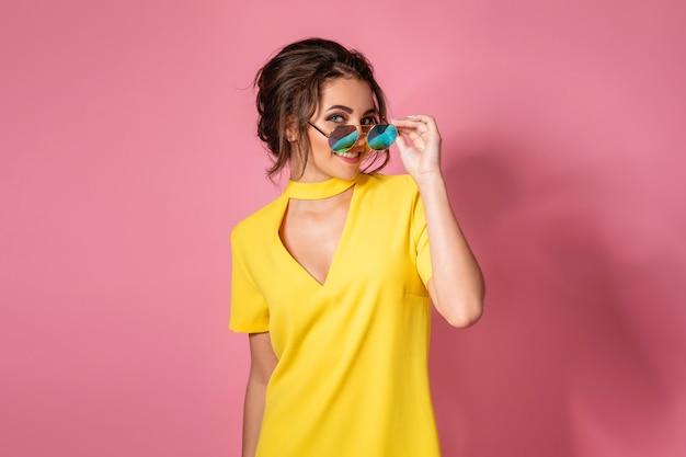 Schönes mädchen im gelben kleid, das die sonnenbrille aufwirft, die auf rosa raum im studio lächelt