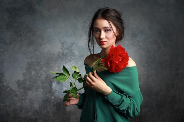 Schönes mädchen im grünen kleid mit blumenpfingstrosen in den händen auf hellgrauem hintergrund. freudiges asiatisches weibliches modell, das im studio mit blumenstrauß der frühlingsblumen aufwirft