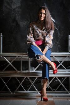 Schönes mädchen im hemd mit blumendruck, kurzen weiten jeans und der rosa ledergürteltaschenaufstellung