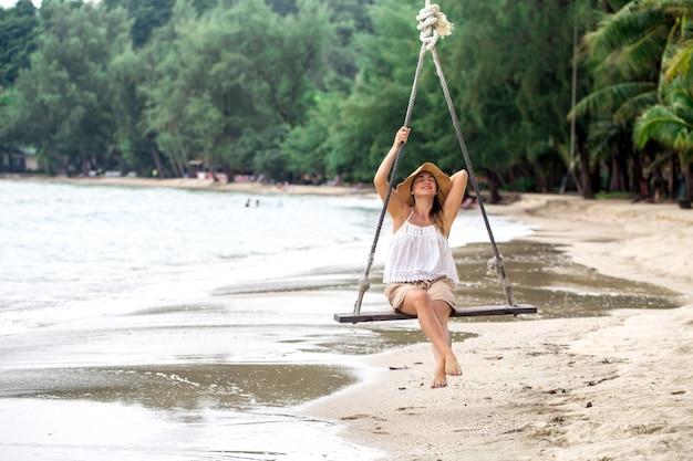 Schönes mädchen im hut auf der hängenden schaukel am strand von thailand