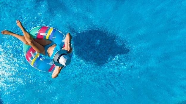 Schönes mädchen im hut in der draufsicht der swimmingpoolluft von oben, junge frau entspannt sich und schwimmt auf aufblasbarem ringdonut und hat spaß im wasser auf familienurlaub, tropisches ferienzentrum
