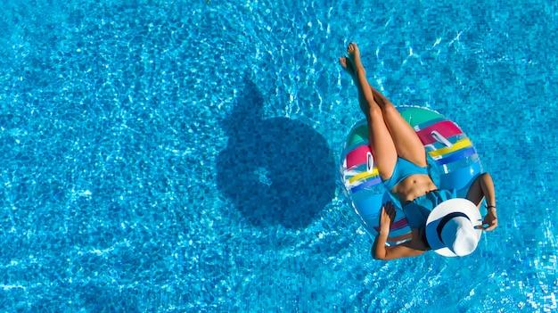 Schönes mädchen im hut in der luftansicht des schwimmbades von oben, junge frau entspannt und schwimmt auf aufblasbarem ringkrapfen und hat spaß im wasser im familienurlaub, tropischer ferienort
