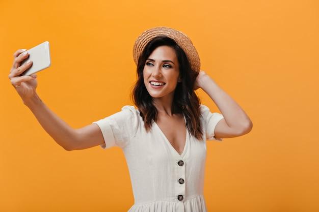 Schönes mädchen im hut macht glücklich selfie auf orange hintergrund. charmante lächelnde frau im leichten modischen kleid macht foto.