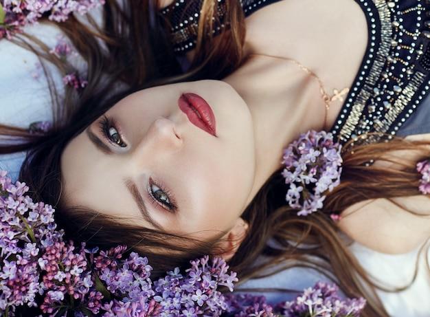Schönes mädchen im kleid, das an einem sommertag in lila zweigen liegend posiert, lila blumen im park. frühlingsporträt eines träumenden mädchens in der natur unter der sonne. gemischte gefühle im gesicht