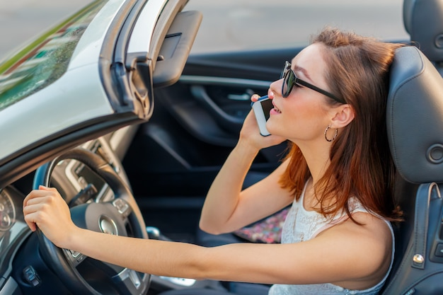 Schönes mädchen im konvertierbaren cabrio auto an einem sonnigen tag in einer stadt