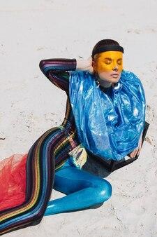 Schönes mädchen im kreativen festival-outfit, gelbe plastikmaske und blau glänzende haube
