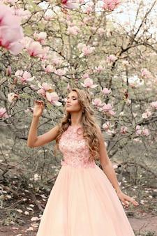 Schönes mädchen im langen rosa fattinikleid, das handbauch berührt und blühende magnolie im park betrachtet.