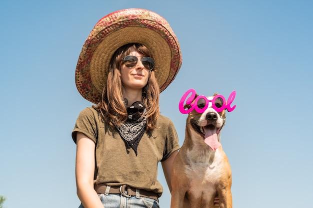 Schönes mädchen im mexikanischen hut verkleidet als gangster des gangsters mit hund in der kühlen sonnenbrille. weibliche person in sombrerohut und bandana, die mit welpen als festliches symbol mexikos oder für halloween aufwirft