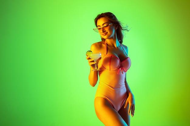 Schönes mädchen im modischen badeanzug einzeln auf steigungsstudiohintergrund im neonlicht. sommer-, resort-, mode- und wochenendkonzept