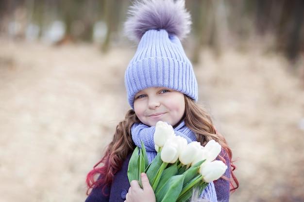 Schönes mädchen im park mit einem blumenstrauß der weißen tulpen. strauß tulpen. blumen als geschenk zum muttertag der frau. 8. märz. das konzept des frühlings und des frauentags. ostern. nahaufnahmeporträt chil