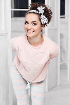 Schönes mädchen im pyjama lächelnd, hände hinter ihrem rücken