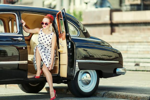 Schönes mädchen im retrostil und in einem weinleseauto